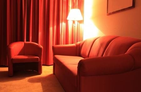 Hotel interior with red couch, armchair and floor lamp