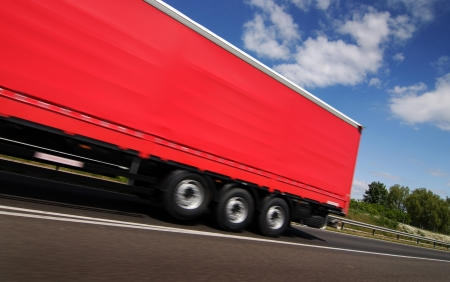 Red truck, lorry driving on country-road under blue sky