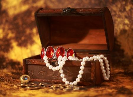 cofre tesoro: Tesoro lleno de joyas y un brazalete de perlas pecho