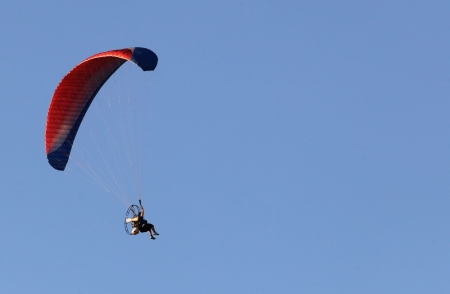 Paragliding man against blue sky