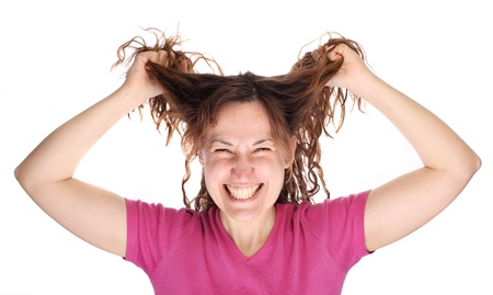 ruffle: Young smiling tearing her hair out in despair  Isolated on white Stock Photo