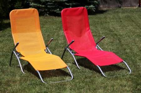 sunbed: Red and yellow sunbed on grass outdoor Stock Photo