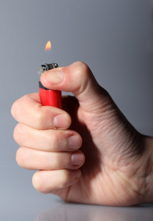 Hand igniting red cigarette lighter Stock Photo - 15366118