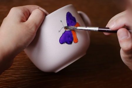 Artist paint colorful butterfly on cup