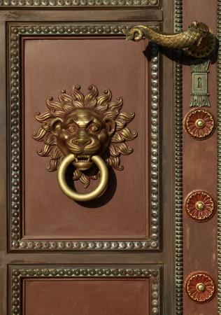 doorknocker: Door handle and door knocker with lion head Stock Photo
