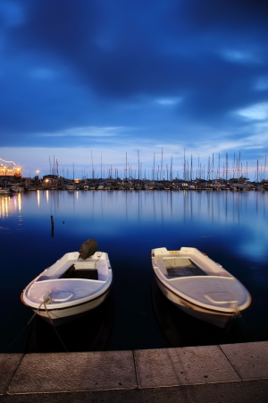docking: Two white boats floating on water at blue sky Stock Photo