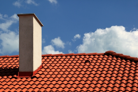home repair: Red tiles roof and chimney with blue sky