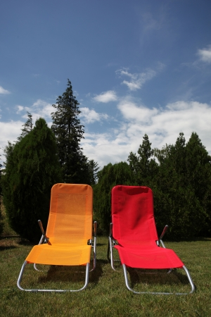 elbow chair: Red and yellow sunbed on grass outdoor Stock Photo