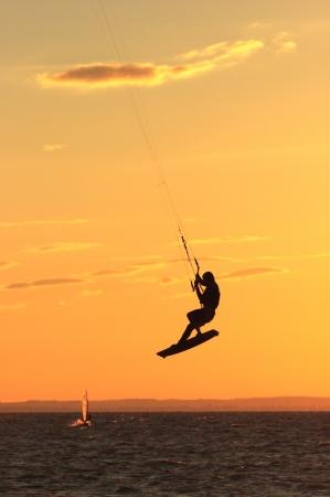 Kitesurfer in de lucht vliegen op kleurrijke zonsondergang