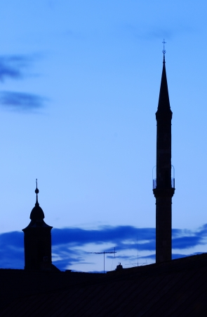 mohammedan: Silhouette of a minaret tower and a church tower at night