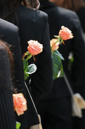 Graduating in black costume with roses
