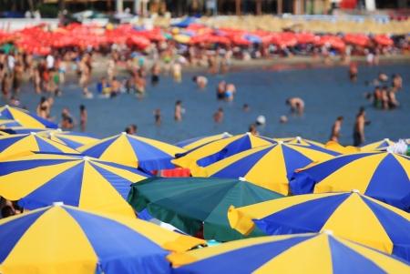 beach umbrella: Stripped beach umbrellas people in background
