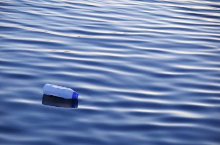 kunststof fles: Plastic fles drijvend op het oppervlak van het water