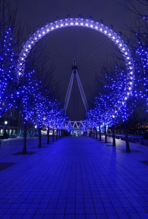 Pavement to London Eye, big wheel the famous symbol of London at night in purple color