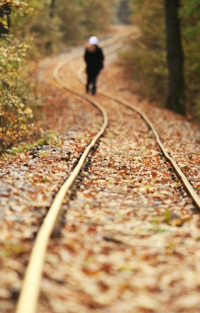 Train track covered with fallen leaves in autumn with walking person photo