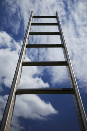 Ladder reaching into a blue sky and clouds photo