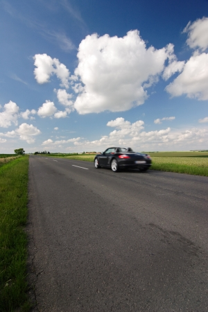 Cabriolet car drive on road, blue sky with beautiful clouds photo
