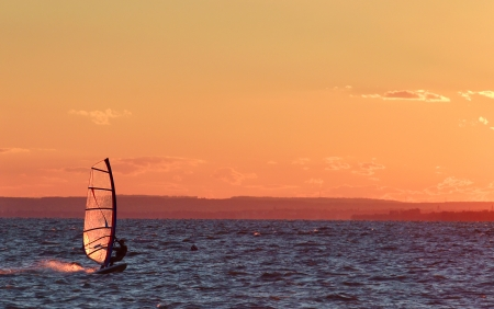Windsurfer go fast on lake beautiful colors at sundown  photo