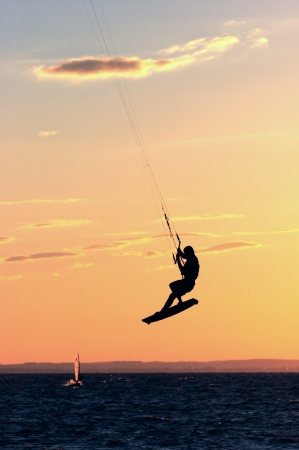 Kitesurfer fly in the air at colorful sundown