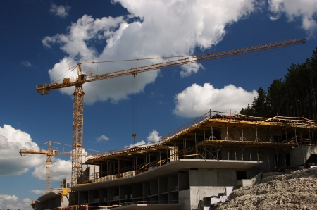 Concrete building built with tower crane at nice cloudy sky
