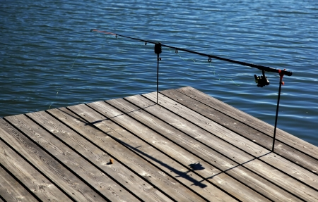 One fishing pole on pier Stock Photo - 16129937
