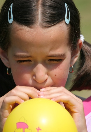 dilate: Young girl is blowing yellow balloon Stock Photo