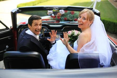 Young wedding couple waving in cabriolet car Foto de archivo