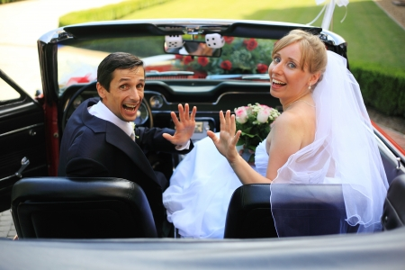 bridal hair: Young wedding couple waving in cabriolet car Stock Photo