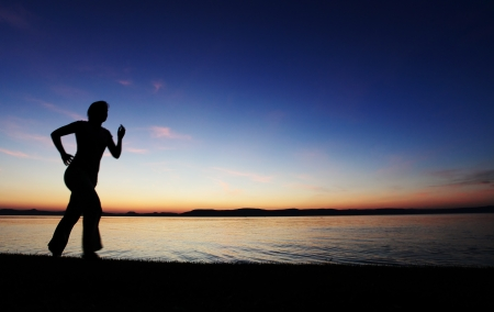 Young woman running on a beach at sunset Stock Photo