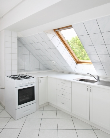 Tiled kitchen in attic with sink and oven photo