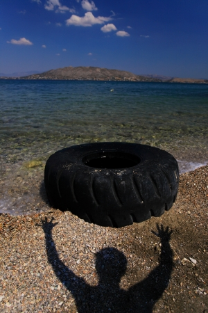 Seashore with abandoned tyre with man of silhouette photo