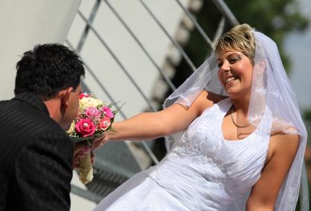 Groom smells his bride s bouquet outdoor photo