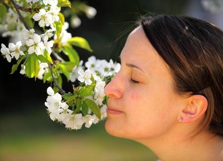 inhale: Pretty young women smells flower outdoor