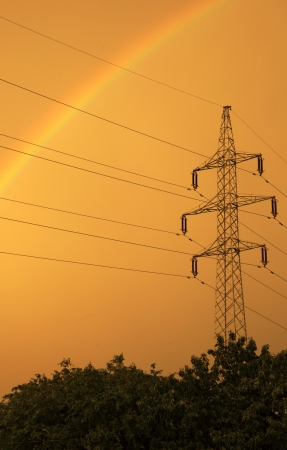 High-voltage electrical power transmission tower with rainbow again yellow sky photo
