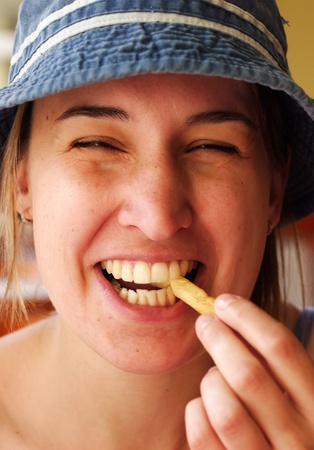 Young woman laugh and eating french fries photo