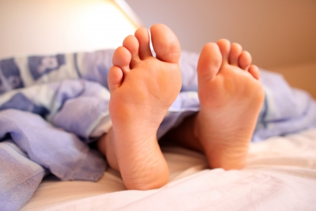 Young woman s bare feet in bed photo