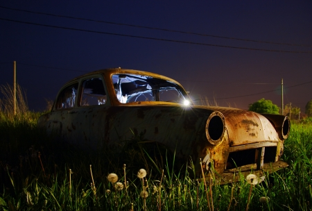 Abandoned rusted car wreck at night photo