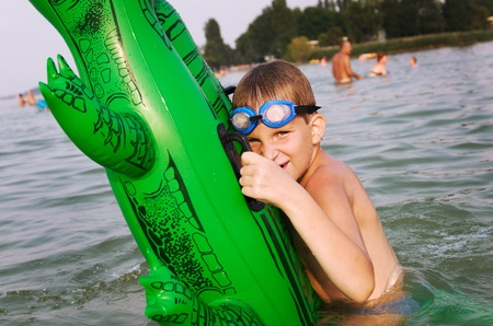 floater: Young boy hold his green floater crocodile in the water