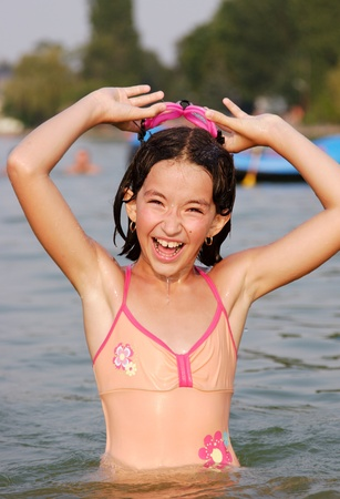 buoyant: Nice young girl smile in the water in summer