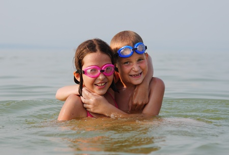 lido: Happy brother and sister embrace each other in the water