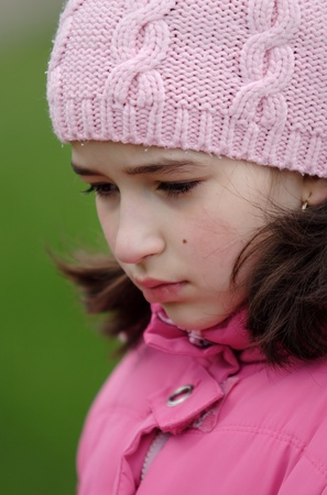 outcast: Sad girl in pink cap look depressed Stock Photo
