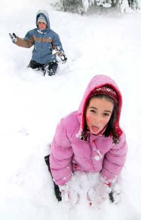 Playful girl child lies on the snowfield