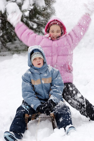 toboggan: Brother and sister sitting on toboggan in winter