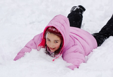 snowfield: Playful girl child lies on the snowfield