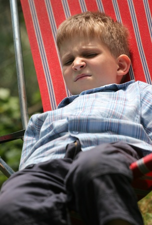 whining: Bored young boy is sitting in striped chair