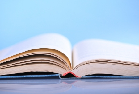 Open book on blue background Stock Photo - 18529674