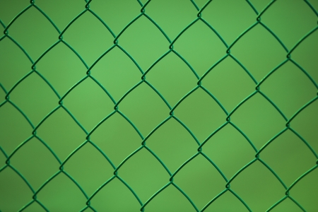 Chain link fence with green background photo