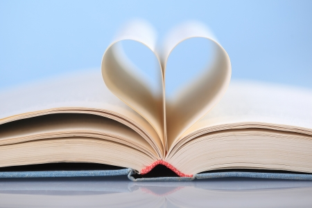 Pages of a book curved into a heart shape on blue background Stock Photo - 18824304