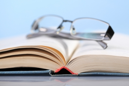 Open book on blue with eyeglasses photo