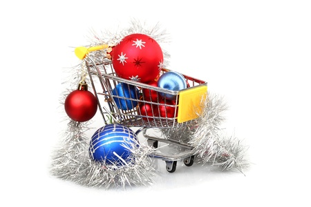 Christmas baubles inside shopping trolley on white background photo